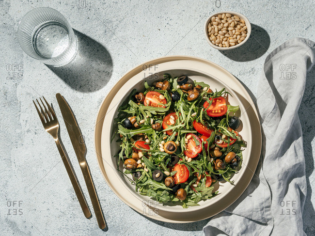 Salad with arugula, mini champignons, cherry tomatoes, black olives, pine nuts. Top view or flat lay. Copy space. Hard light. Horizontal