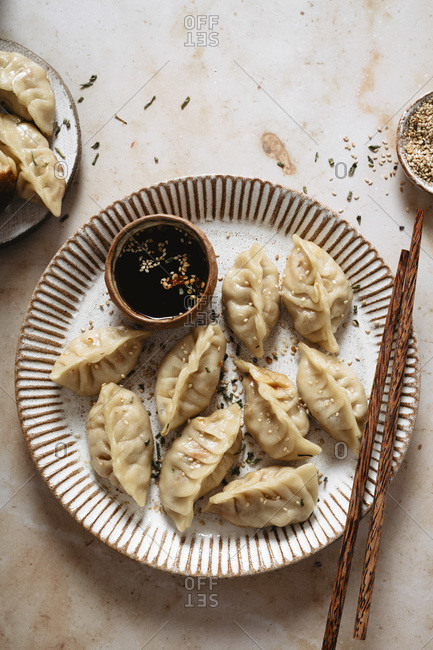 Pot stickers filled with chicken, on a plate with chopsticks