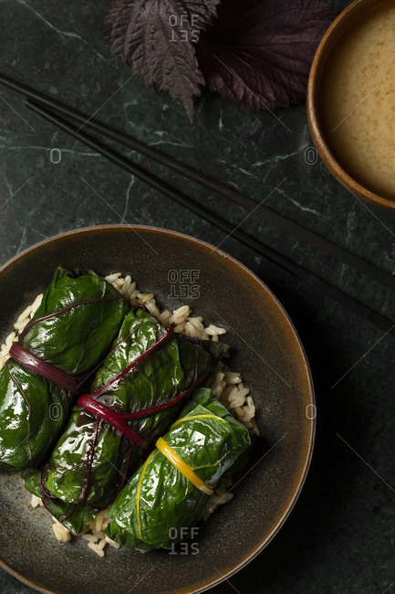 Japanese inspired rainbow chard rolls, filled with mushrooms and finished in a miso broth. They are served on  brown rice in a brown stoneware bowl, with miso soup and chopsticks alongside.