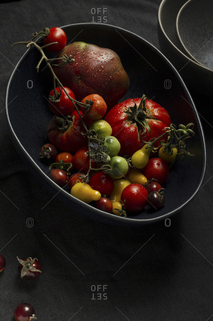 A selection of various heirloom tomatoes in a large, dark blue free form bowl. There is a stack of grey dishes in the background and loose cherry tomatoes on a charcoal linen tablecloth in the foreground.