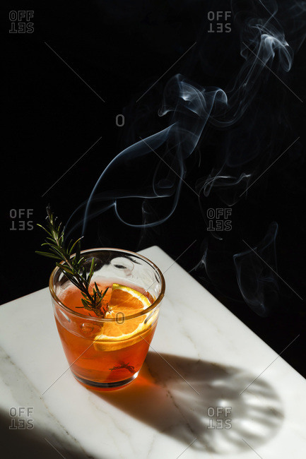 Negroni cocktail with a slice of orange and a smoking rosemary sprig garnish. The view features the corner of a marble tabletop with the shadow of the dimpled glass.