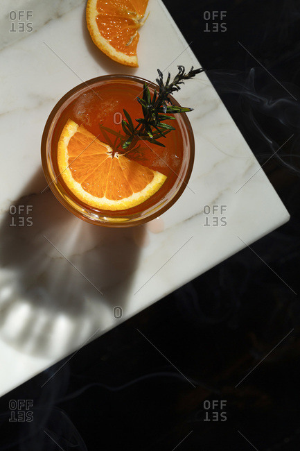 Negroni cocktail with a slice of orange and a smoking rosemary sprig garnish. The view is overhead looking down onto a marble tabletop with a slice of orange. The shadow of the glass features.
