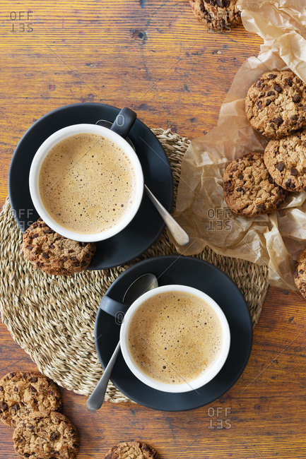 Cups of cappuccino coffee with chocolate chip cookies on baking paper.