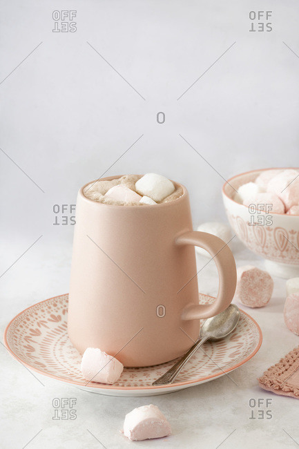 Hot chocolate in a mug with a bowl of pink and white marshmallows.