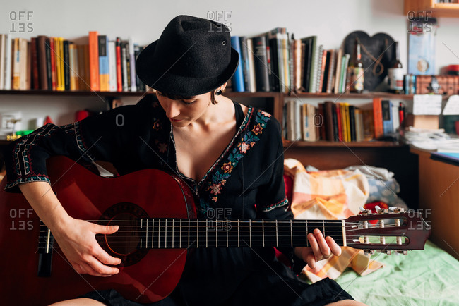 Tranquil female in trendy clothes sitting on bed and playing music on acoustic guitar