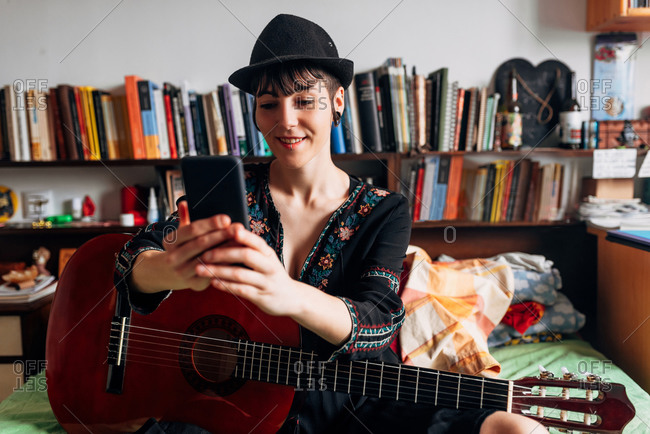 Smiling female in trendy wear and hat sitting on bed with acoustic guitar and reading messages on cellphone while chilling during weekend