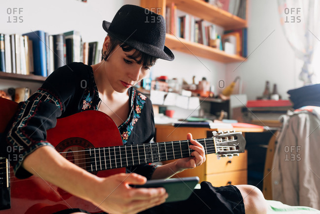 Female in trendy wear and hat sitting on bed with acoustic guitar and reading messages on cellphone while chilling during weekend