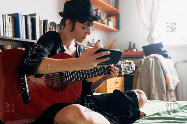 Female in trendy wear and hat sitting on bed with acoustic guitar and cellphone while chilling during weekend