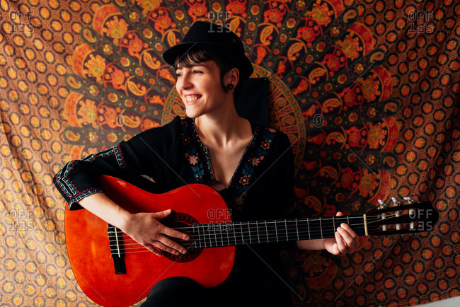 Delighted female hipster in trendy hat and dress leaning on colorful wall cover and playing acoustic guitar