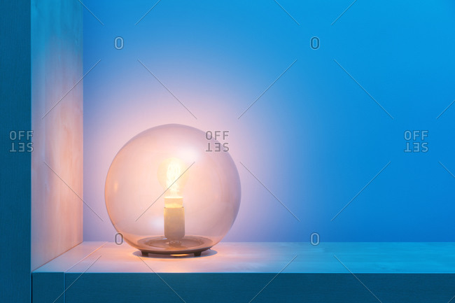Stylish round lamp with glowing yellow light inside of glass ball locating on shelf in dark room with blue walls