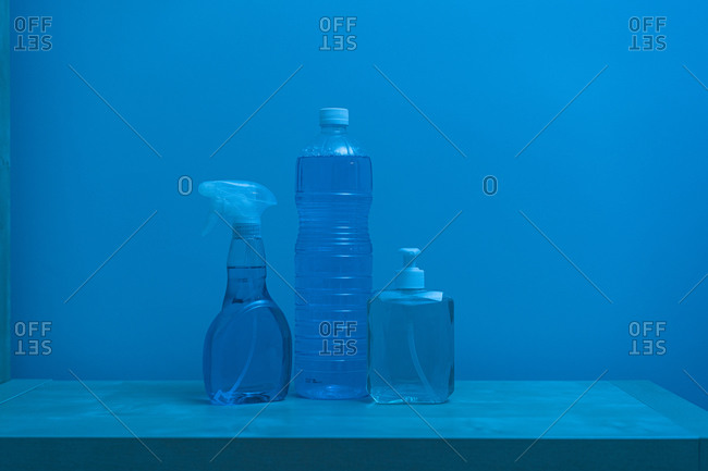 Plastic transparent bottles of different sizes and shapes with colorless liquid inside and white lids locating on shelf against blue wall
