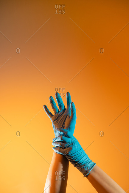 Anonymous medic in disposable surgical gloves touching wrist on orange background in studio