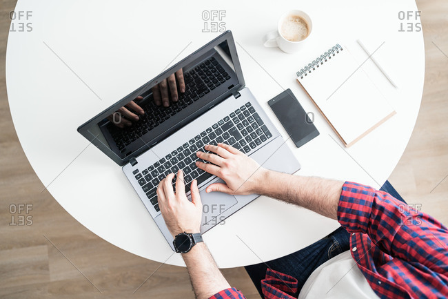 An anonymous man is working from home. The entrepreneur is typing on a computer from above