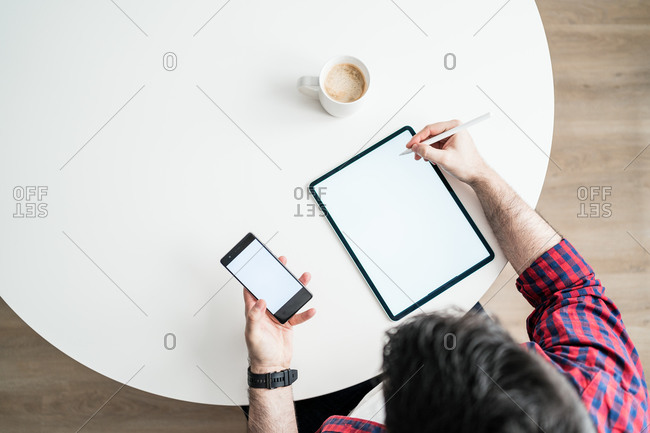 An anonymous man is writing on a blank tablet. The man is working from home. The entrepreneur is holding a phone from above