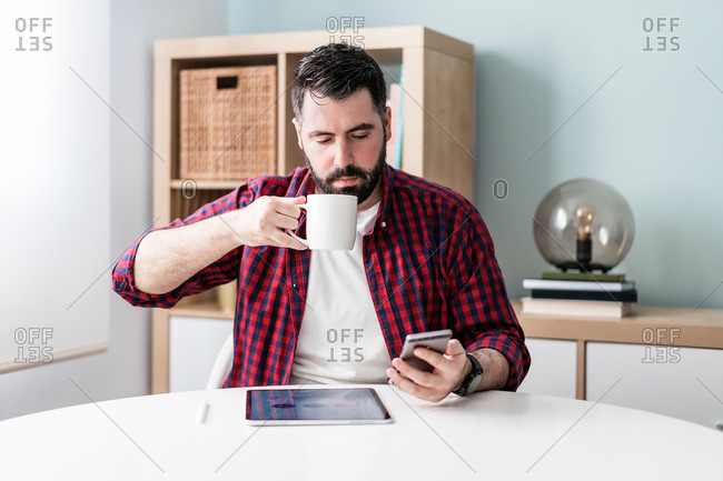 A young man is looking at the mobile phone. The man is working from home. The entrepreneur is holding a phone and drinking from a mug