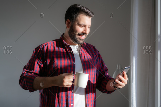 A young man is looking at the mobile phone. The man is working from home. The entrepreneur is holding a phone and drinking from a mug. He is smiling
