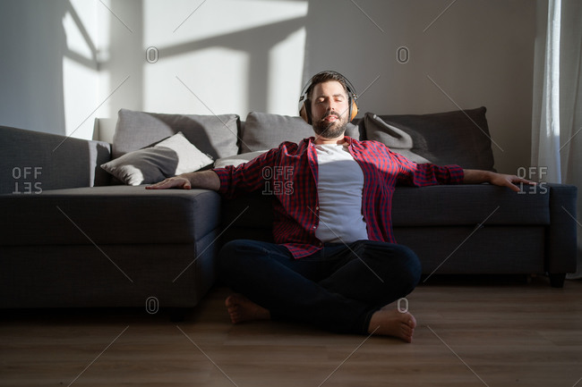 A portrait of a young man enjoying music. The man is wearing a shirt and jeans. He is listening to music in headphones and he is sitting on the floor