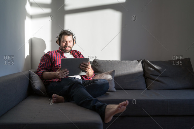 A portrait of a young man enjoying with a tablet. The man is wearing a shirt and jeans. He is watching films and he is sitting on the sofa