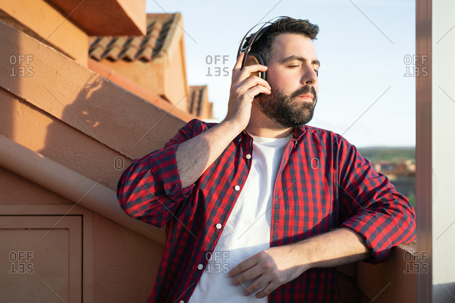 A portrait of a young man while listening to music outside.