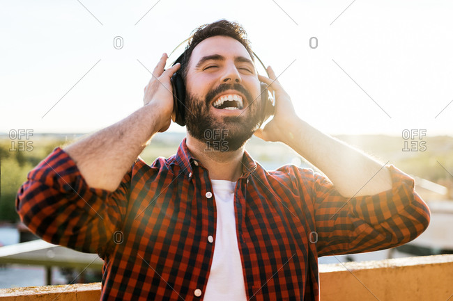 A portrait of a young man while listening to music outside. He is smiling and happy