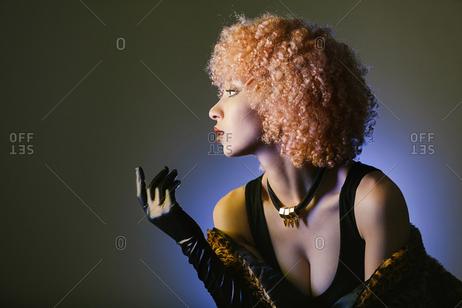 Portrait of stylish ethnic female with leopard fur shawl and necklace with outstretched arm looking away