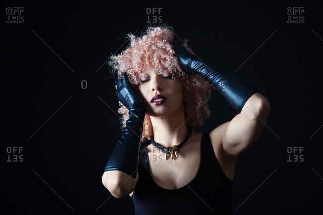 Provocative female in short black dress with raised hands in leather gloves and closed eyes