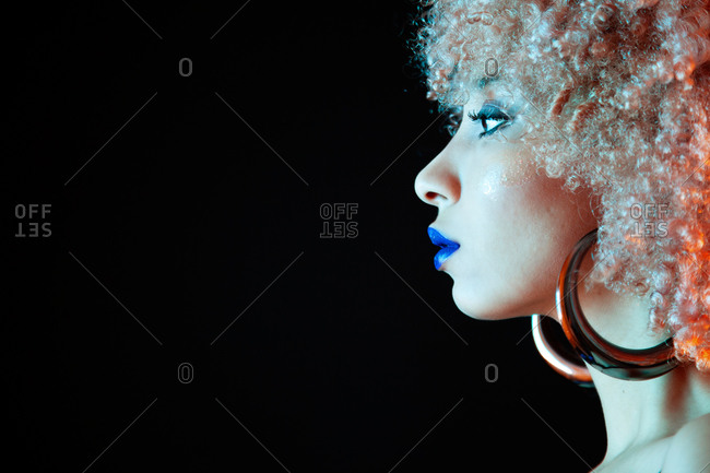 Crop stylish ethnic with blond Afro hairstyle wearing violet lipstick with golden earrings looking away while standing on black background