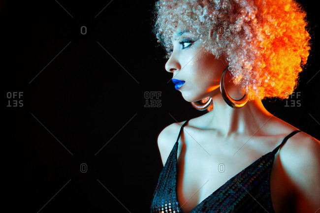Crop stylish ethnic with blond Afro hairstyle wearing violet lipstick and elegant black dress with golden earrings looking away while standing on black background