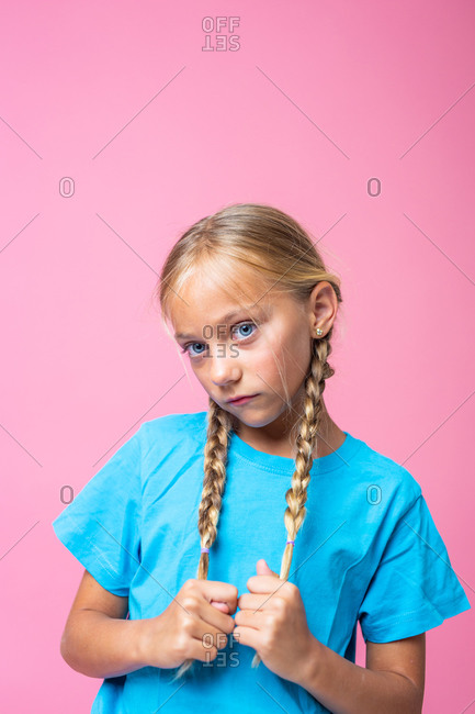 Cute girl with blond braids and in blue t shirt looking at camera against pink background