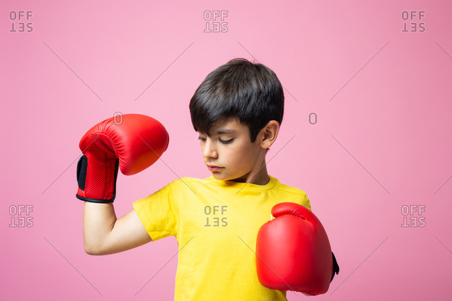 Little boy in yellow t shirt and red boxing gloves looking at camera and hitting air while practicing against pink background