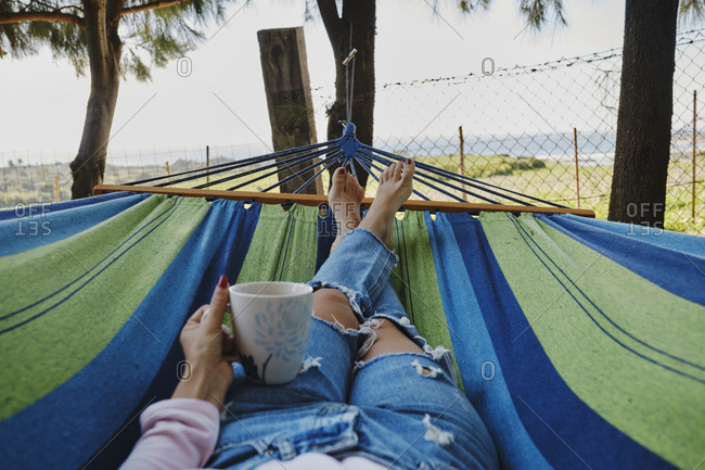 Crop female in jeans lying in hammock with cup of hot coffee and enjoying tropical landscape during summer vacation