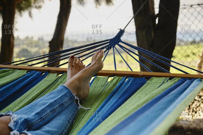 Crop female wearing casual jeans relaxing barefoot in hammock while enjoying weekend in summer