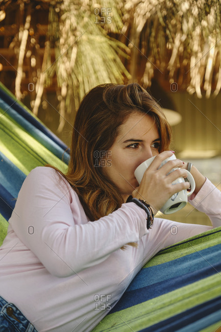 Crop Calm female in casual outfit sitting in hammock drinking mug of hot drink in courtyard and enjoying summer holiday