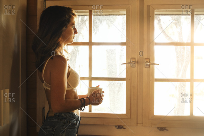 Side view of serene female in bra and jeans standing near window with cup of hot beverage and enjoying weekend in wooden cabin
