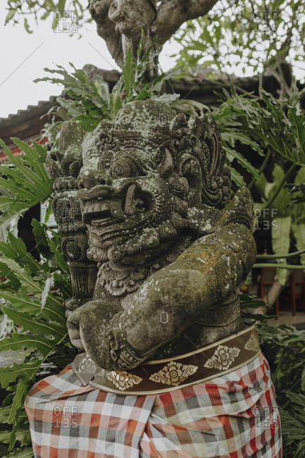 Low angle of statue of Demon surrounded by green tropical foliage in Bali