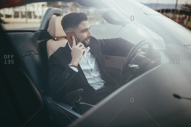 Businessman talking on the phone inside a car