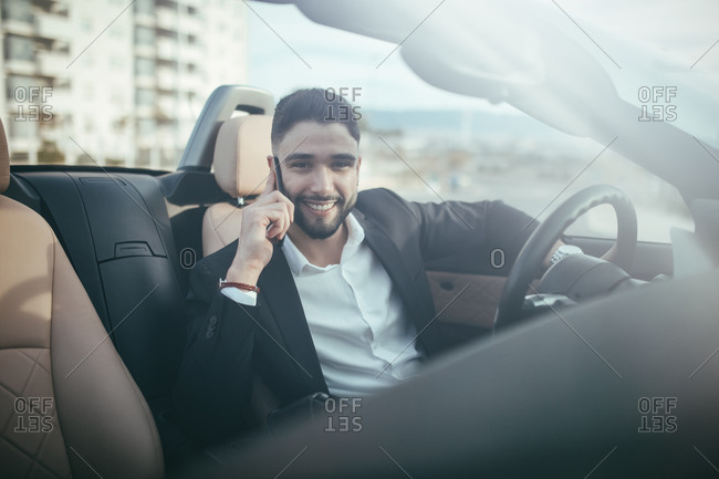 Front view of businessman talking on the phone inside a car