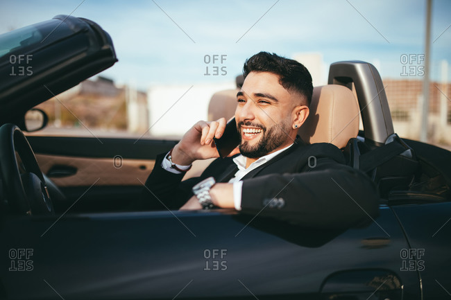 Side view of businessman talking on the phone inside a car at the morning