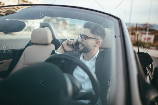 Businessman with glasses talking on the phone inside a convertible car.