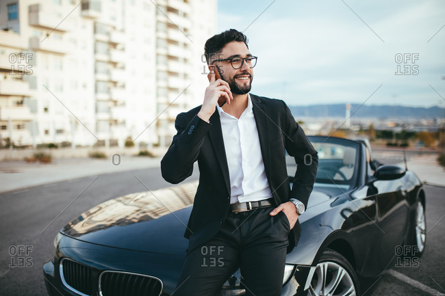 Businessman with glasses talking on the phone outside a convertible car.
