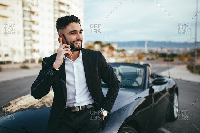 Side view of businessman talking on the phone outside a convertible car.