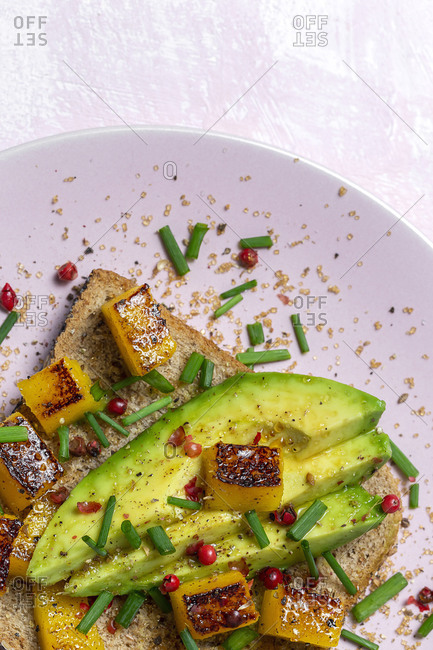 Homemade toasted bread with avocado, mango and aromatic herbs on pink background. Vegetarian food. Healthy food concept.