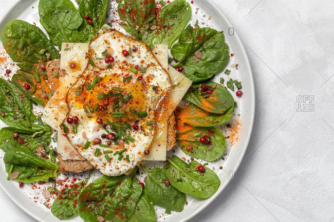 Homemade toasted bread with fried egg, spinach and aromatic herbs on white background. Vegetarian food. Healthy food concept.