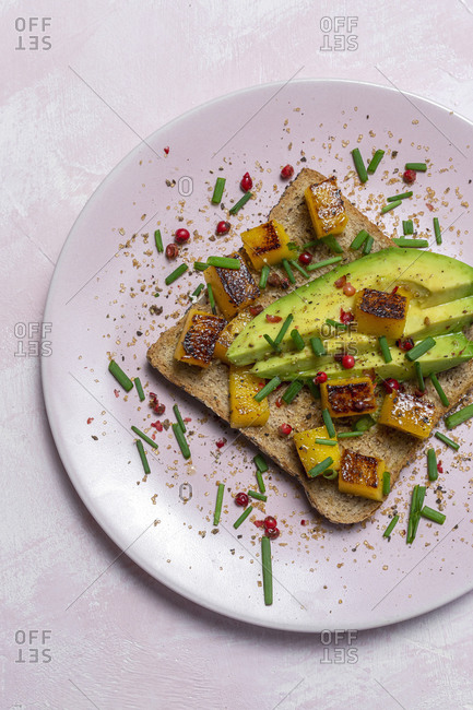 Homemade toasted bread from above with avocado, mango and aromatic herbs on pink background. Vegetarian food. Healthy food concept.