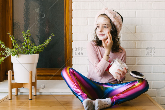 Positive little girl in casual clothes and pink headband sitting on table with potted houseplant and applying face mask from glass jar against background of white brick wall with wooden window