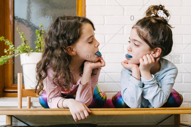 Two smiling sisters sticking out a blue tongue after eating a blue bubble gum