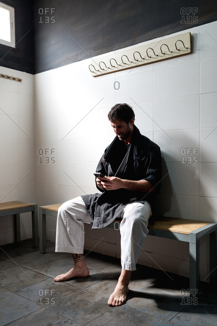 Positive adult barefooted male in kimono sitting on bench in dressing room and browsing smartphone while resting after training in martial arts school