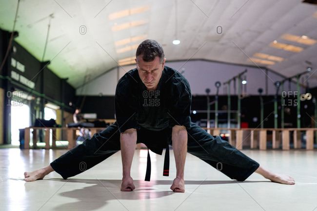 Full body kajukenbo male fighter with closed eyes in kimono performing stretching legs exercise during training in contemporary martial arts club with sports equipment