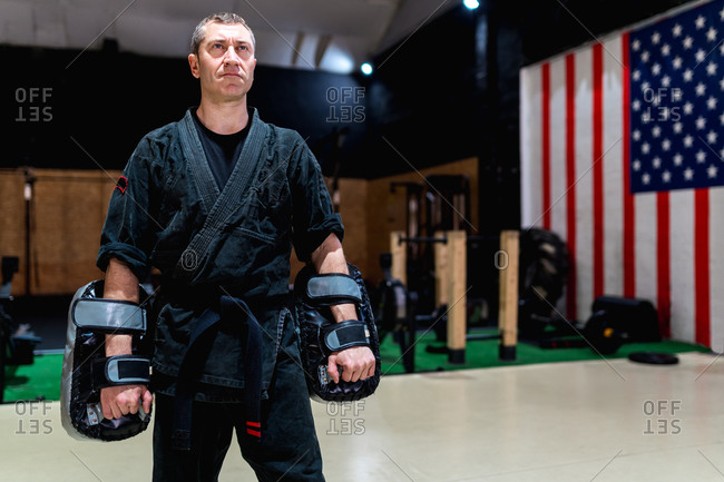 Powerful adult martial arts master in black kimono and boxing pads standing in modern club with sports equipment and American flag