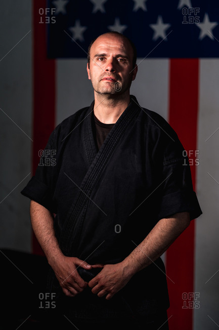 Serious adult martial arts master in black uniform standing against American flag and looking at camera